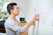 Pensive young Asian UX designer looking at documents with wireframes hanging on wall in office