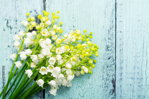 Poster Muguet de mai bunch of lily of the valley flowers on faded blue table, directly above