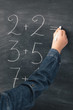 Primary school concept. Young kid studying mathematics, doing sum on chalkboard.