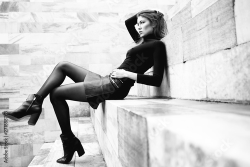Fashion model. Young blond caucasian woman dressed in black clothes. Beautiful caucasian girl posing outdoor in Milan, Italy. Street fashion.