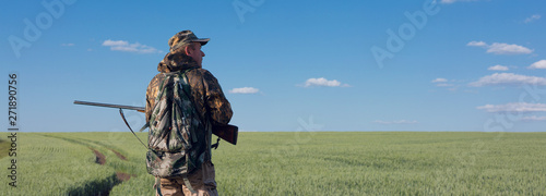 Fotografia Silhouette of a hunter with a gun in the reeds against the sun, an ambush for du