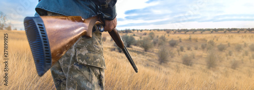 Foto Silhouette of a hunter with a gun in the reeds against the sun, an ambush for du