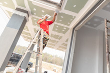 Construction Worker Are Plastered A Ceiling. Concept Build A House