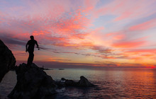 Silhouette Of Fisherman On The Rock At Amazing Sea Sunset