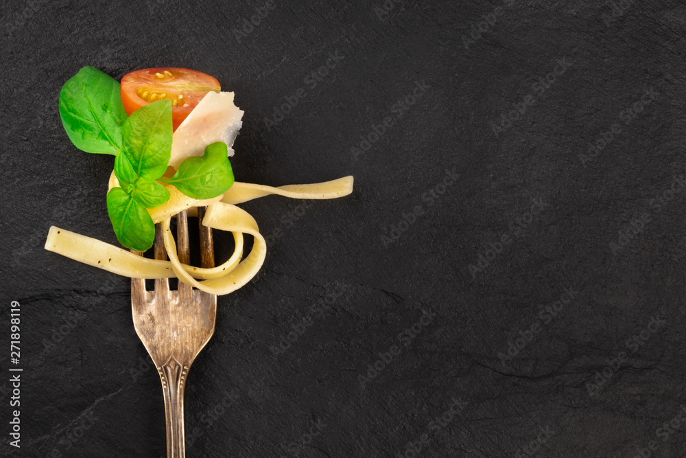 Fototapety, obrazy: Italian pasta design. A closeup of a fork with pappardelle, basil, Parmesan cheese, tomato, and pepper, shot from above on a dark background with a place for text