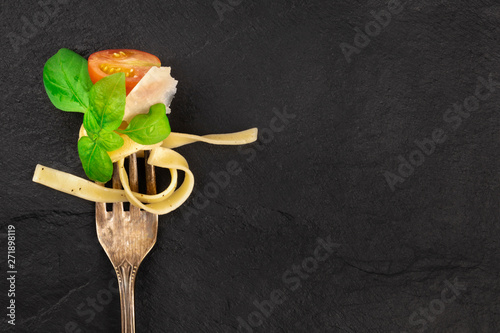 Obraz Italian pasta design. A closeup of a fork with pappardelle, basil, Parmesan cheese, tomato, and pepper, shot from above on a dark background with a place for text - fototapety do salonu