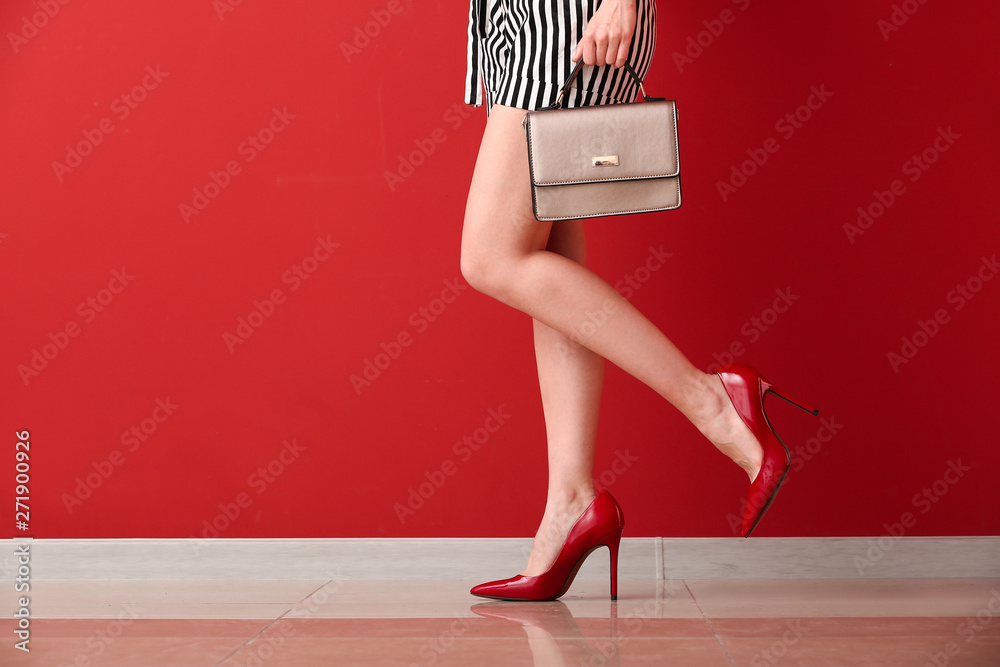 Fototapety, obrazy: Young woman in high-heeled shoes near color wall