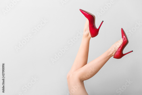 Fotografía  Legs of young woman in high-heeled shoes on light background