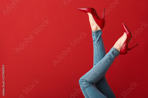 fototapeta na szkło Legs of young woman in high-heeled shoes on color background