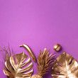 Leinwandbild Motiv Golden exotic fruits, tropical palm, monstera leaves on violet background. Top view. Flat lay. Food concept. Creative layout of gold pineapple, banana, lemon with copy space.