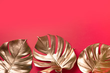 Exotic Summer Trend In Minimal Style. Golden Tropical Palm Monstera Leaf On Red Color Background. Shiny And Sparkle Design, Fashion Concept.