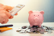 Leinwandbild Motiv Hand Calculate Saving Money with Piggy bank account Income and Profit with Calculator