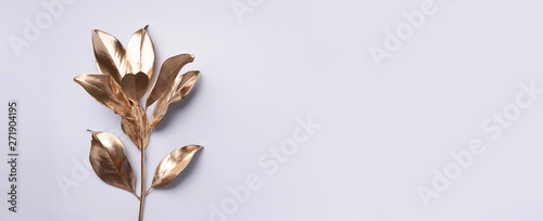 Floral minimal style concept. Exotic summer trend. Golden tropical leaves and branch on grey color background. Shiny and sparkle design, fashion concept.
