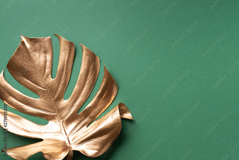 Fototapeta Golden tropical monstera leaf on nude background with copy space. Top view. Flat lay. Creative layout. Exotic summer concept in minimal style