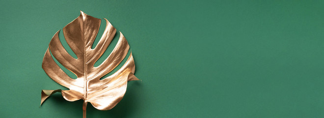 Exotic summer trend in minimal style. Golden tropical palm monstera leaf on pastel green color background. Shiny and sparkle design, fashion concept.