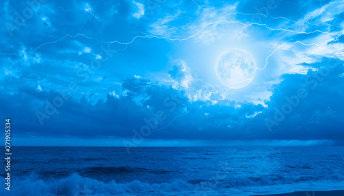 Poster Mer / Ocean Night sky with full moon in the clouds on the background lightning