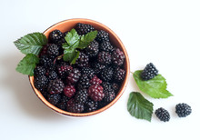 Black Raspberries With Leaves On A Plate.