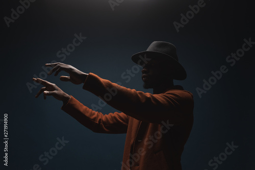 Vászonkép Portrait of male singer in hat and coat. Artist, performer