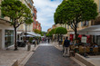 People walking through a narrow street in the center of Monaco on the French Riviera.
