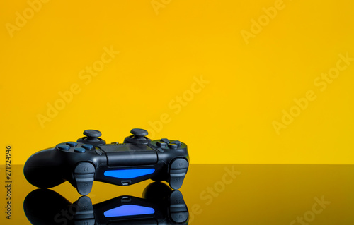 Modern black gamepad on a yellow back. Joystick black color on a smooth reflective table. Gaming concept