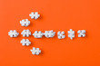 Leinwandbild Motiv top view of white direction arrow with jigsaw puzzle pieces on orange