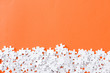 Leinwandbild Motiv top view of unfinished white puzzle pieces isolated on orange with copy space