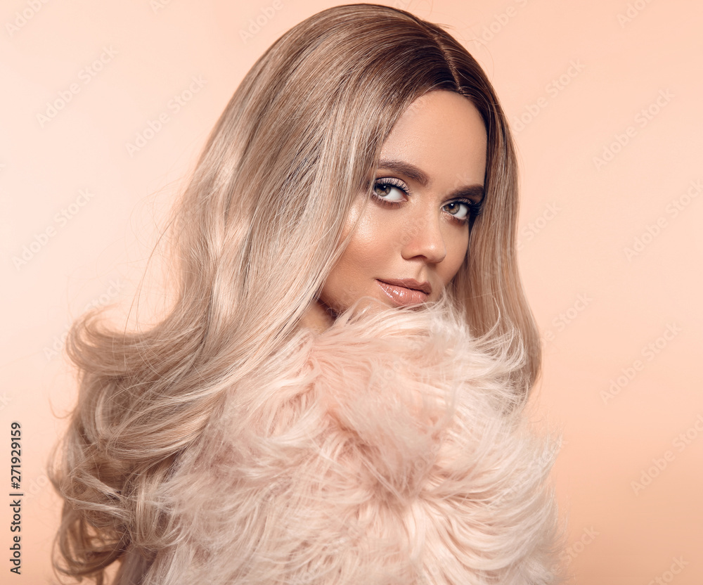 Fototapeta Ombre blond hairstyle. Beauty fashion blonde portrait. Sexy woman wears in pink fur coat. Beautiful girl model with makeup, long healthy hair style posing isolated on studio beige background.