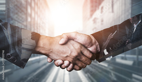 Double exposure image of business people handshake on city office building in background showing partnership success of business deal Fotobehang