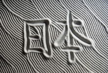 Japanese Zen Garden Raked With The Chinese Characters For Nihon (English Translation: Japan) In Capital Letters In Textured White Sand