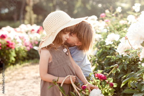 Valokuva  adorable children boy and girl kiss in a peonies garden..