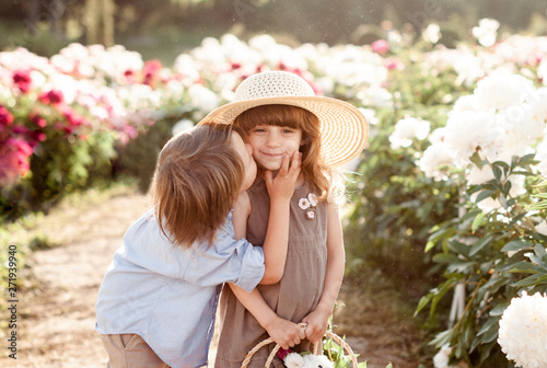 Fotografía  the little boy kisses the pretty girl in a straw hat in the garden of peonies