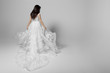 canvas print picture - Back view of a beautiful young woman in wedding flying white princess dress, isolated on a white background. Copy space.