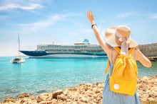 Happy Woman Tourist With Backpack On A Coastline, Looking At The Big Cruise Liner Ship. Purchasing Of Tour And Summer Vacation Concept