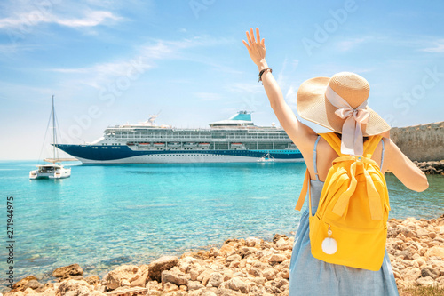 Happy woman tourist with backpack on a coastline, looking at the big cruise liner ship Canvas
