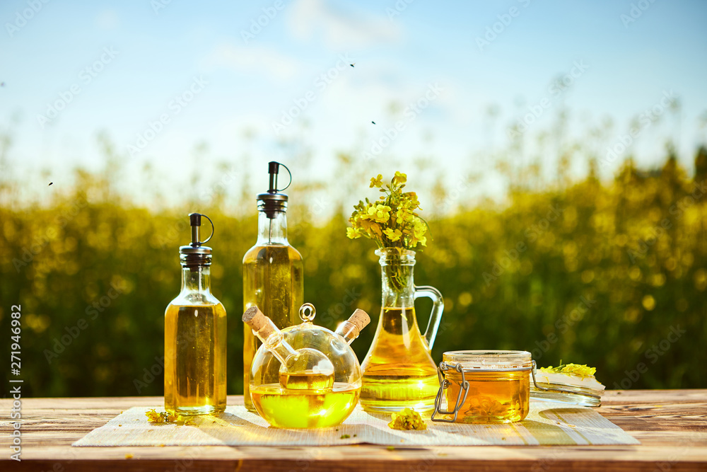 Fototapeta Rapeseed oil bottles (canola) on background rape field