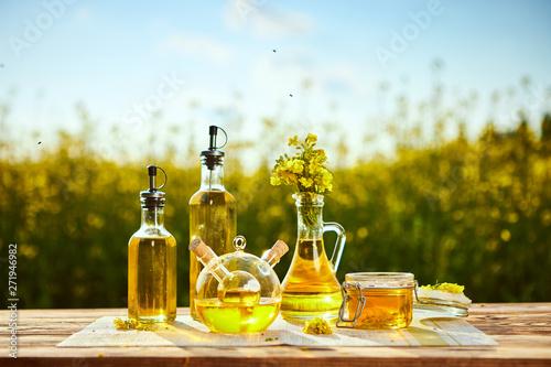 Fototapeta Rapeseed oil bottles (canola) on background rape field obraz