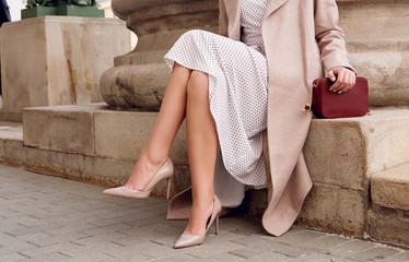 Closeup fashion woman legs in beige high heel shoes, dress.