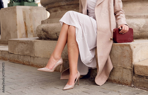 Closeup fashion woman legs in beige high heel shoes, dress.