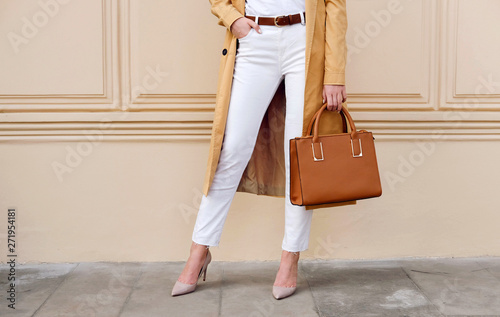 Closeup female legs. Woman in coat with bag. Fashion outfit Canvas Print