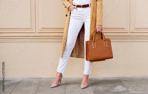 Fotografia  Closeup female legs. Woman in coat with bag. Fashion outfit