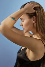 Cropped Side View Shot Of Blonde Lady, Wearing Black Crop Top And Silver Bangle Bracelet With Massive Blue-green Stone. The Woman Is Fixing Hair With Eyes Closed, Standing On Light Blue Background.