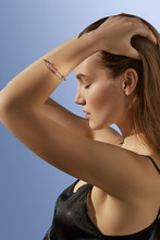 Cropped Side View Shot Of Blonde Lady, Wearing Black Crop Top And Silver Bangle Bracelet With Massive Pale Pink Raw Crystal. The Woman Is Fixing Hair With Eyes Closed, Standing Over Blue Background.