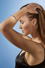 Cropped Side View Shot Of Blonde Lady, Wearing Black Crop Top And Silver Bangle Bracelet With Massive Milky Raw Crystal. The Woman Is Fixing Hair With Eyes Closed, Standing Over The Blue Background.