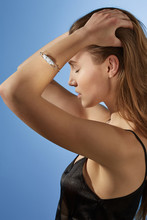 Cropped Side View Shot Of Blonde Lady, Wearing Black Crop Top And Silver Bangle Bracelet With Snowy Raw Crystal. The Woman Is Fixing Hair With Eyes Closed, Standing Over The Light Blue Background.