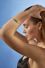 Cropped Side View Shot Of Blonde Lady, Wearing Black Crop Top And Silver Bangle Bracelet With Massive Emerald Green Raw Crystal. The Woman Is Fixing Hair With Eyes Closed Against Blue Background.