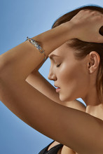 Cropped Side View Shot Of Blonde Lady, Wearing Black Crop Top And Silver Bangle Bracelet With Blue Marble Raw Crystal. The Woman Is Fixing Hair With Eyes Closed, Standing On Light Blue Background.