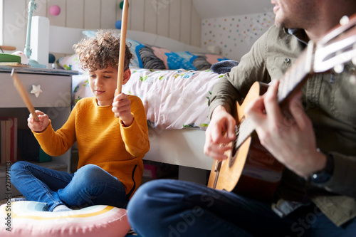 Fototapeta  Single Father Playing Guitar With Son Who Drums On Cushion In Bedroom