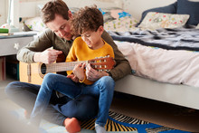 Single Father At Home With Son Teaching Him To Play Acoustic Guitar In Bedroom