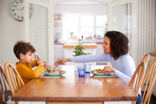 Fototapeta Single Mother Sitting At Table Eating Meal With Son In Kitchen At Home