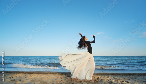Foto auf Leinwand Blau Jeans Classical dancer woman. Charming ballerina with windy hair in white chiffon skirt dancing by the sea background. Sun shines on her. Horizontal.